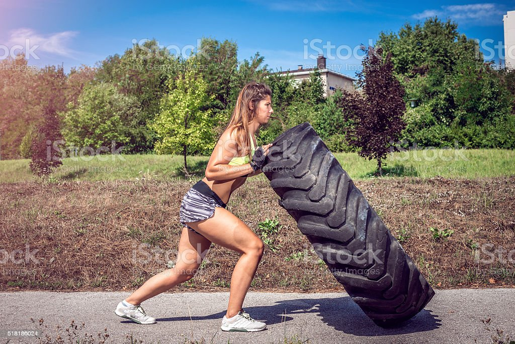 Girl flipping tire during exercise stock photo