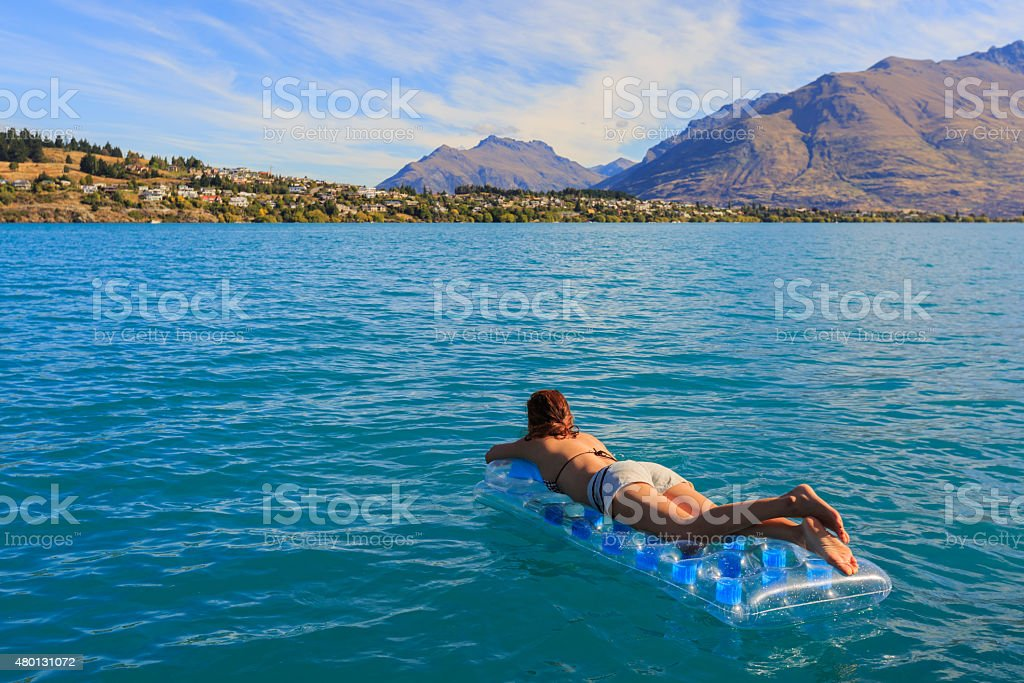 girl floating on a mattress stock photo