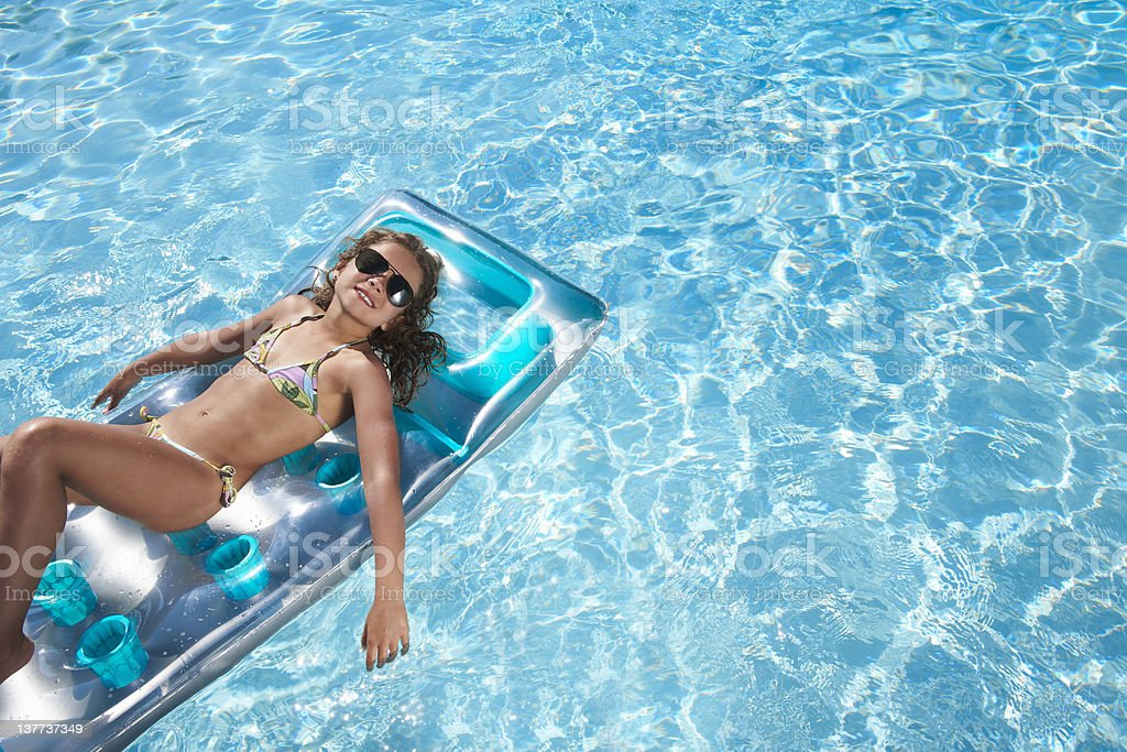 Girl floating on raft in swimming pool royalty-free stock photo