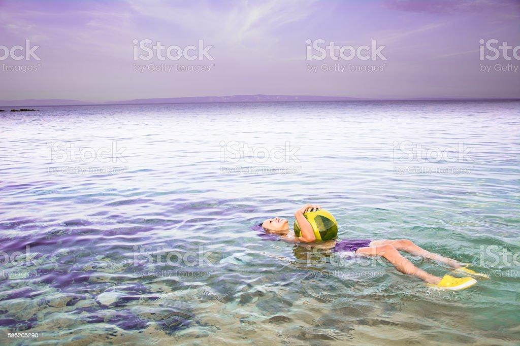 Girl floating on water stock photo
