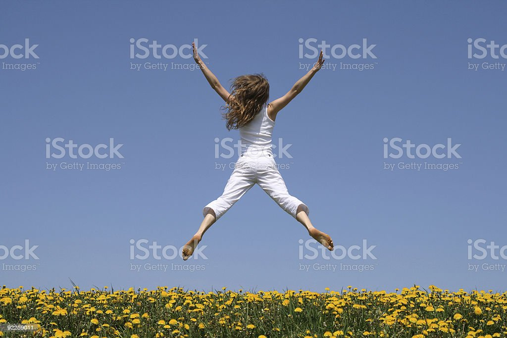 Girl flying in a funny jump over dandelion field royalty-free stock photo