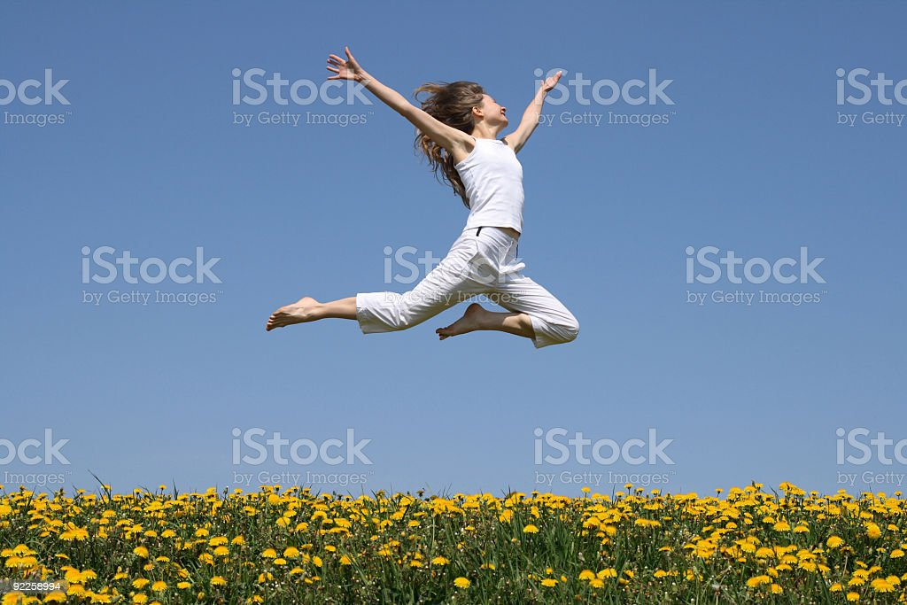 Girl flying in a jump over dandelion field royalty-free stock photo