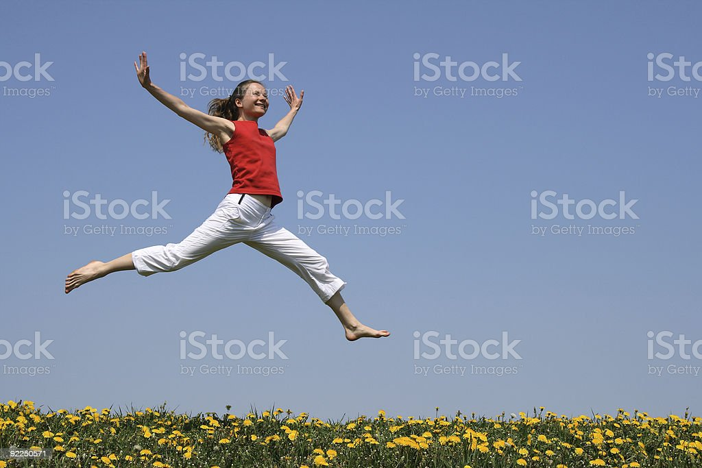 Girl flying in a jump over flowering field royalty-free stock photo