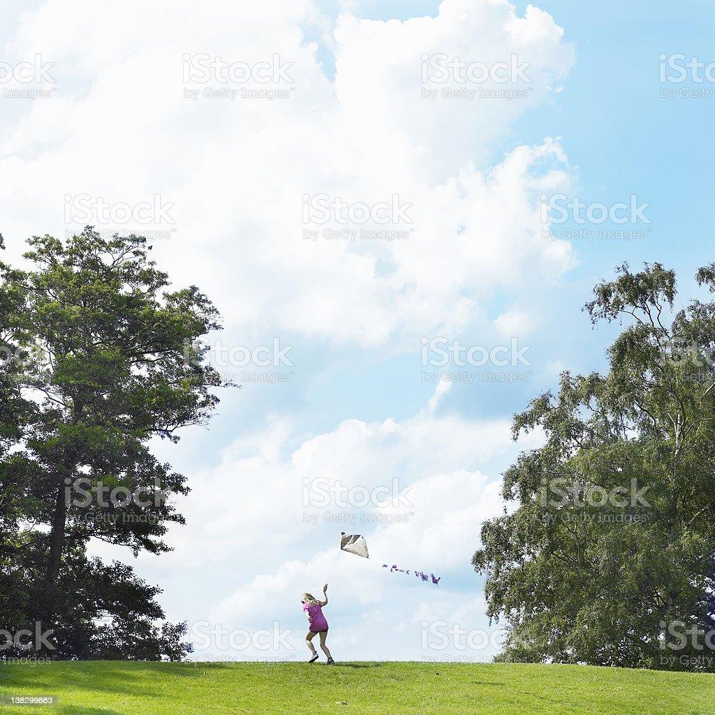 Girl flying kite in field stock photo