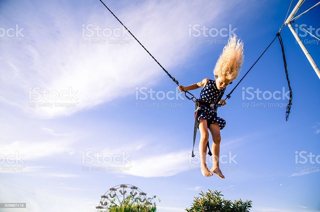 girl flying on bungee attraction stock photo