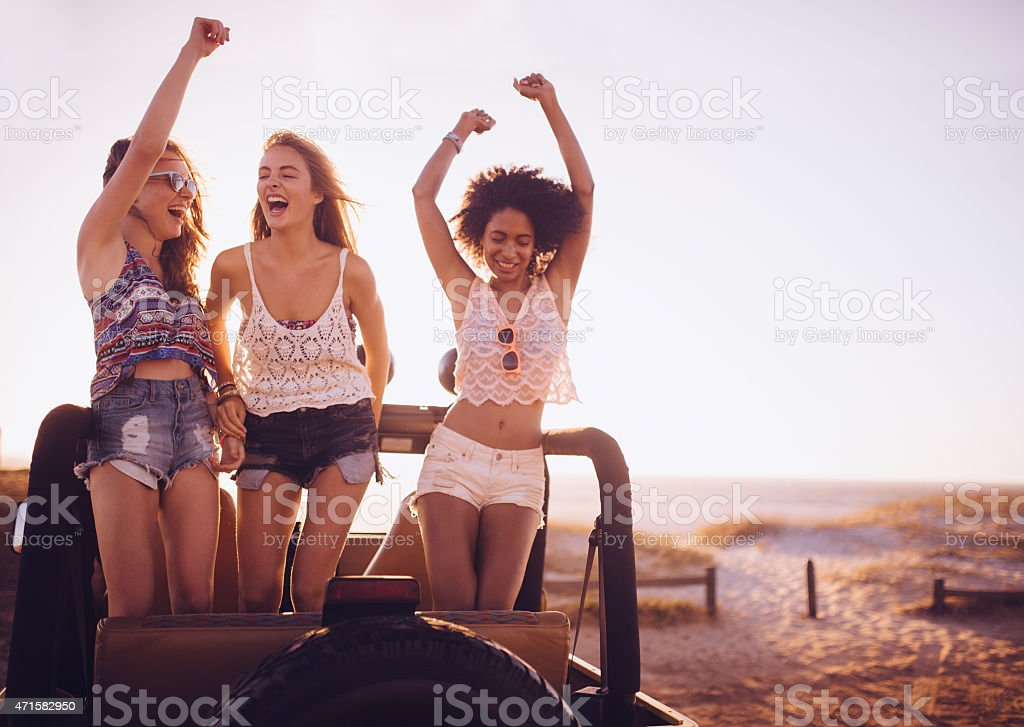 Girl friends dancing in vehicle at beach on road trip stock photo