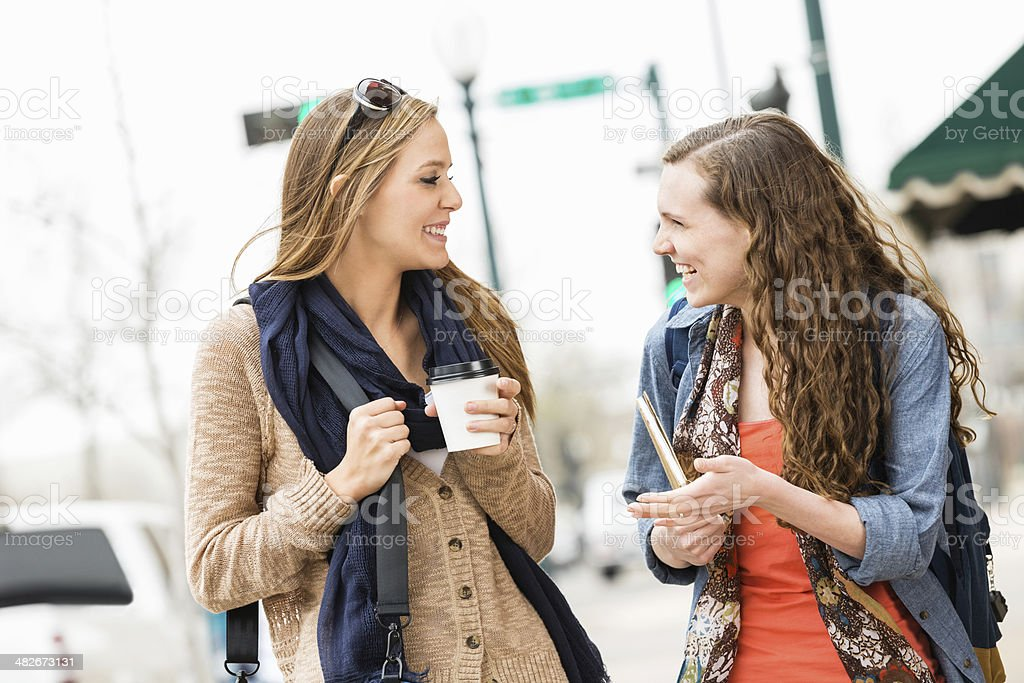 Girl friends walking down city street while having coffee royalty-free stock photo