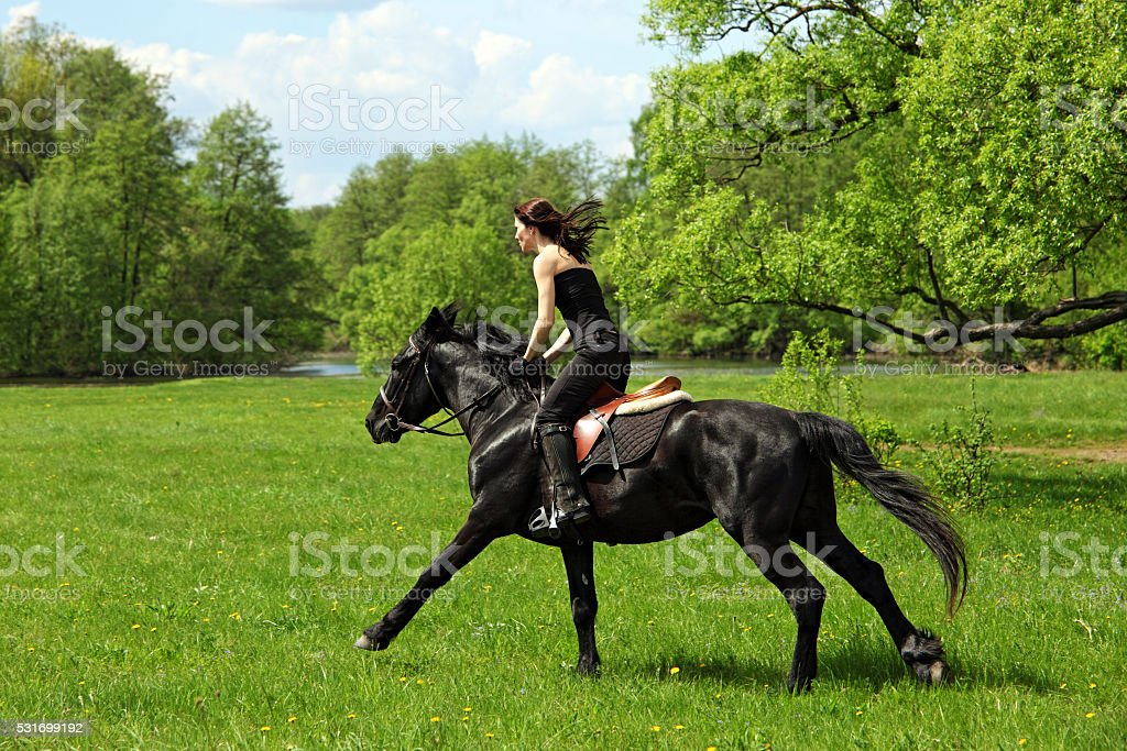 Girl galloping on horseback by summer meadow stock photo