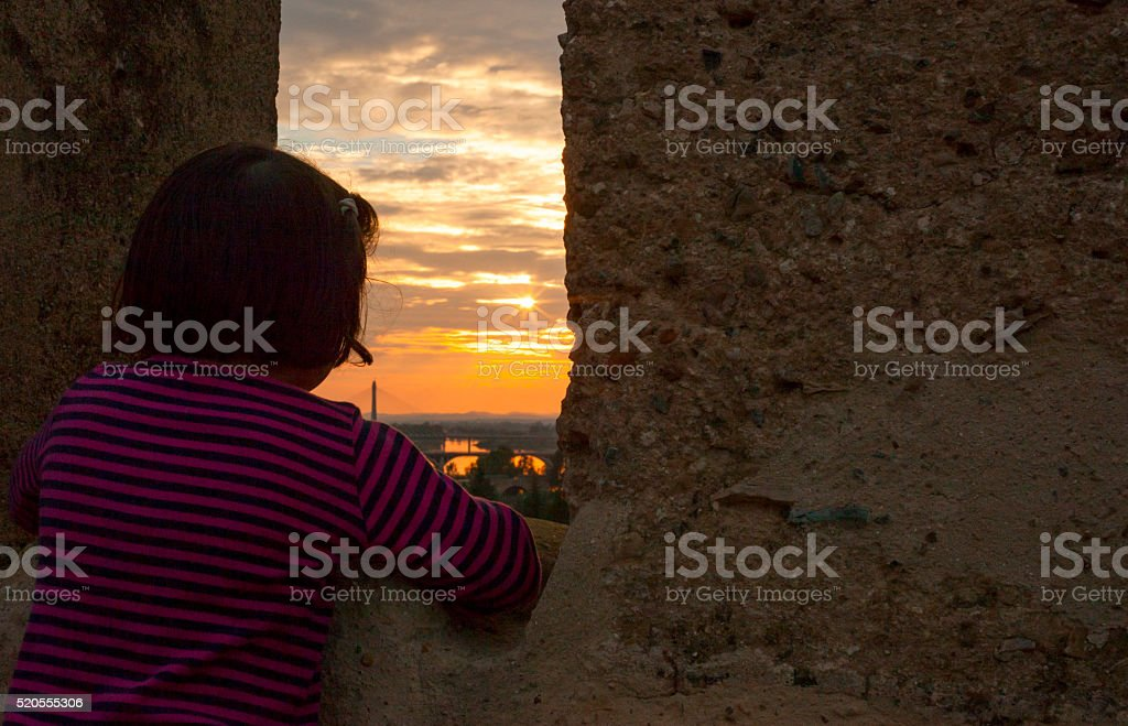 Girl gazing at sunset from the Middle Age wall stock photo