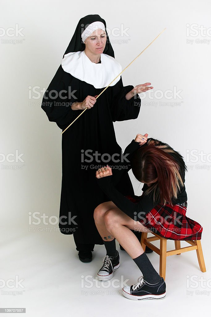 Girl getting in trouble by a nun. stock photo
