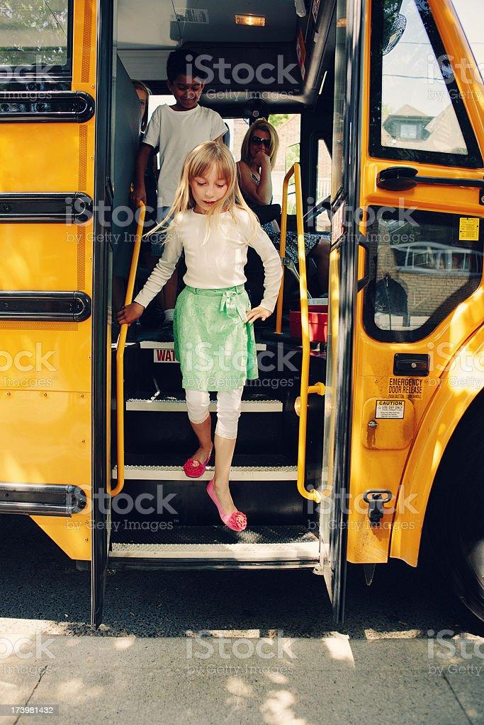 girl getting off school bus stock photo