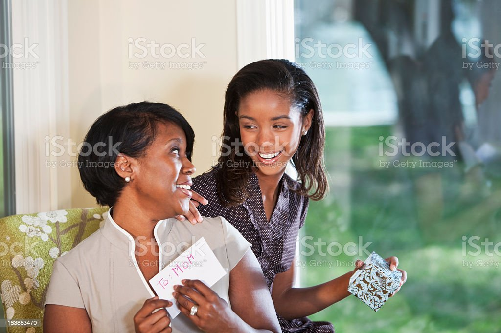 Girl giving gift and card to mother royalty-free stock photo
