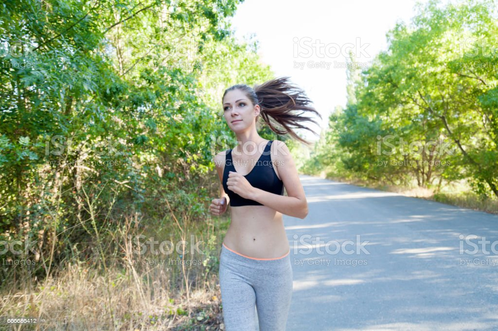 girl goes in for sports runs on a forest road stock photo