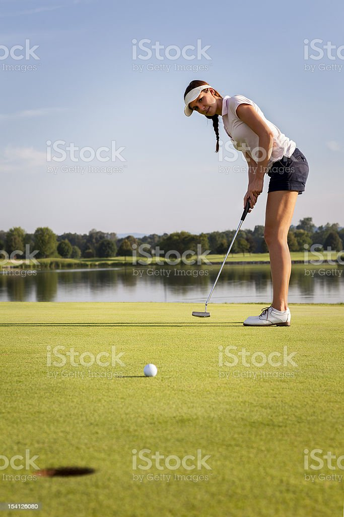 Girl golfer putting ball on green. royalty-free stock photo