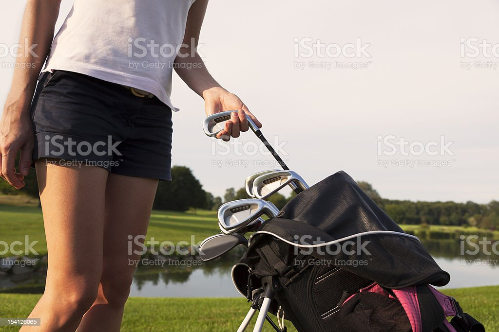 Girl golfer taking out iron from golf bag. royalty-free stock photo