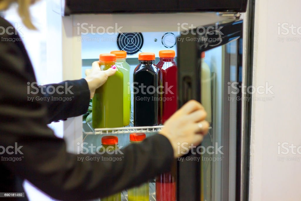 Girl grabbing cold pressed juice from refrigerator stock photo