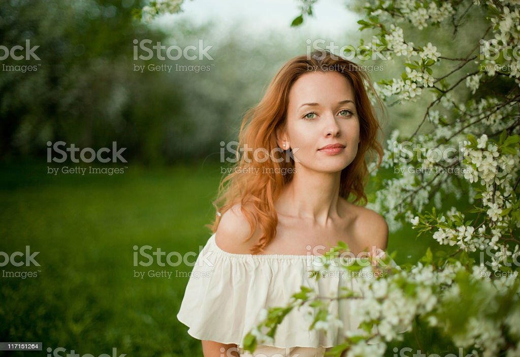 Girl grinning red hair in lush green garden white tree royalty-free stock photo