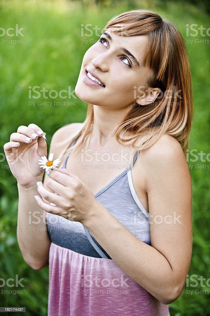 Girl guesses on camomile stock photo