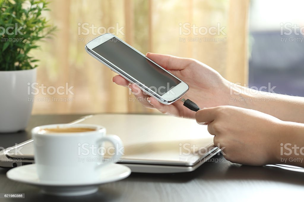 Girl hand connecting charger to smart phone stock photo