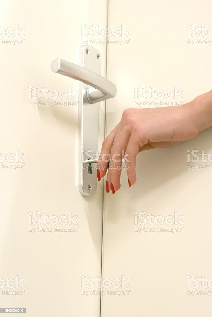Girl hand opening door with key stock photo