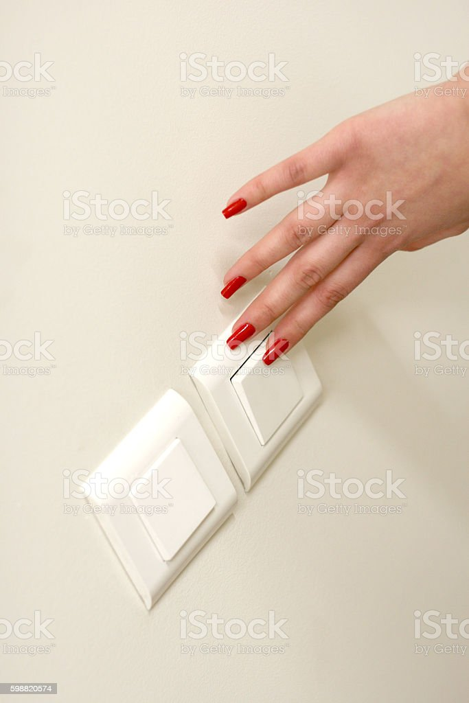 Girl hand turning off the light switch stock photo