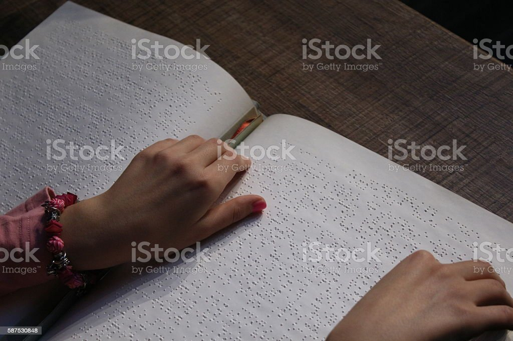 Girl hands reading a braille book with hands stock photo