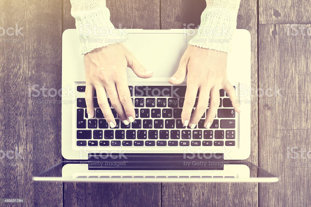 Girl hands typing on laptop on a wooden table stock photo
