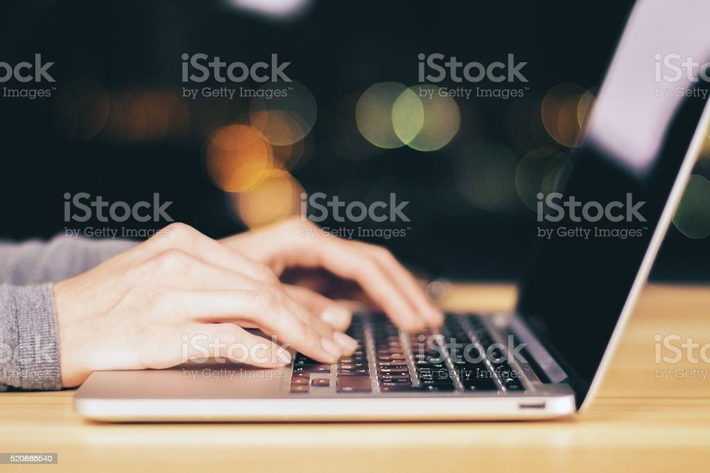 Girl hands typing on laptop on wooden table at night stock photo