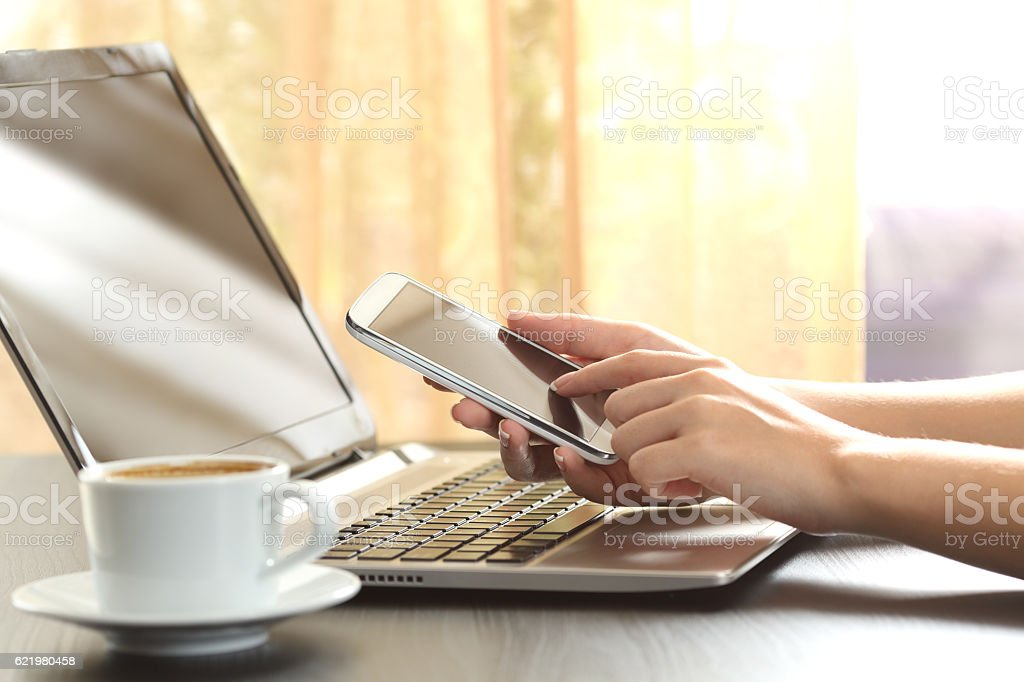 Girl hands using a smart phone and laptop stock photo