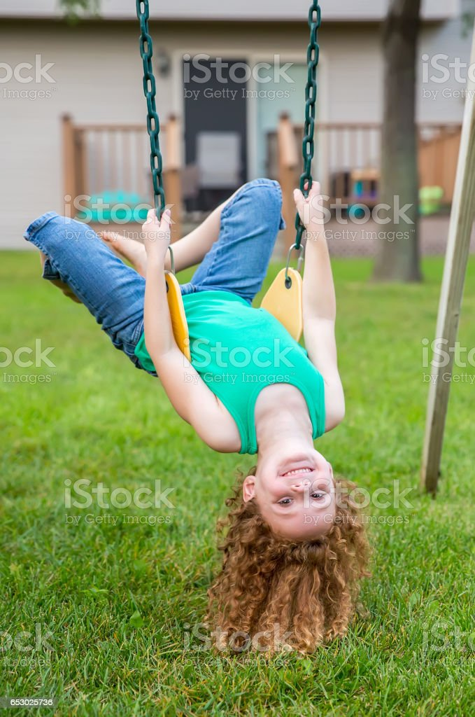 Girl Hanging Upside Down on Backyard Swing stock photo