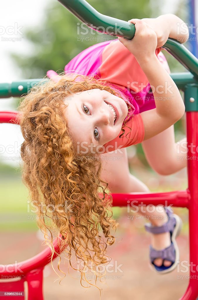Girl Hanging Upside Down on Jungle Gym at Playground stock photo