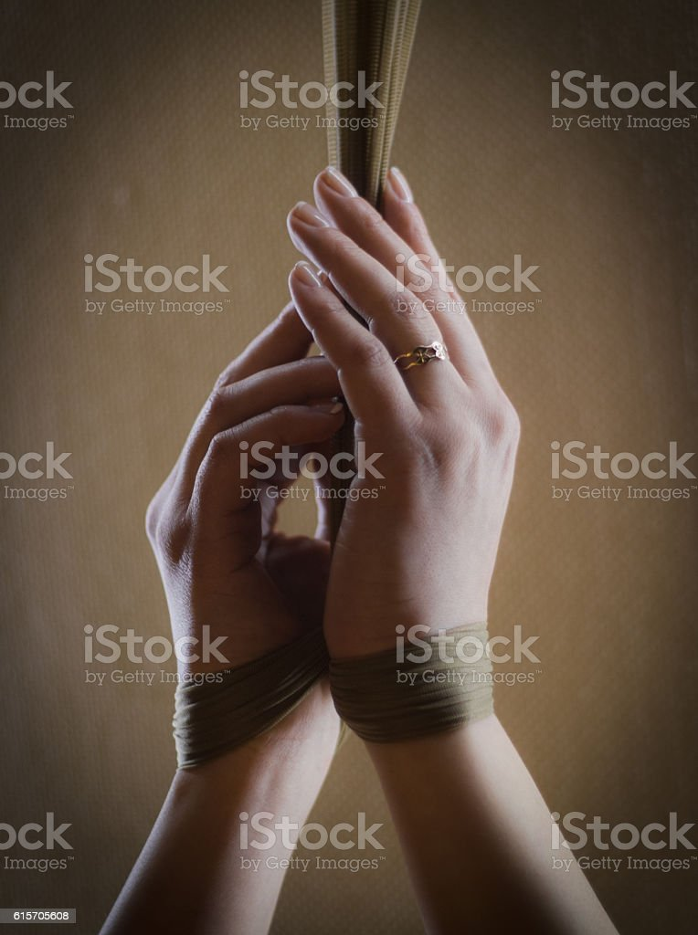 Girl has hands bound with stockings - close up shot stock photo