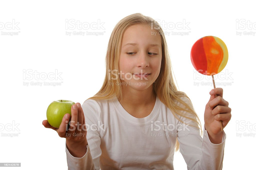 Girl has to decide between an apple and a lollipop royalty-free stock photo