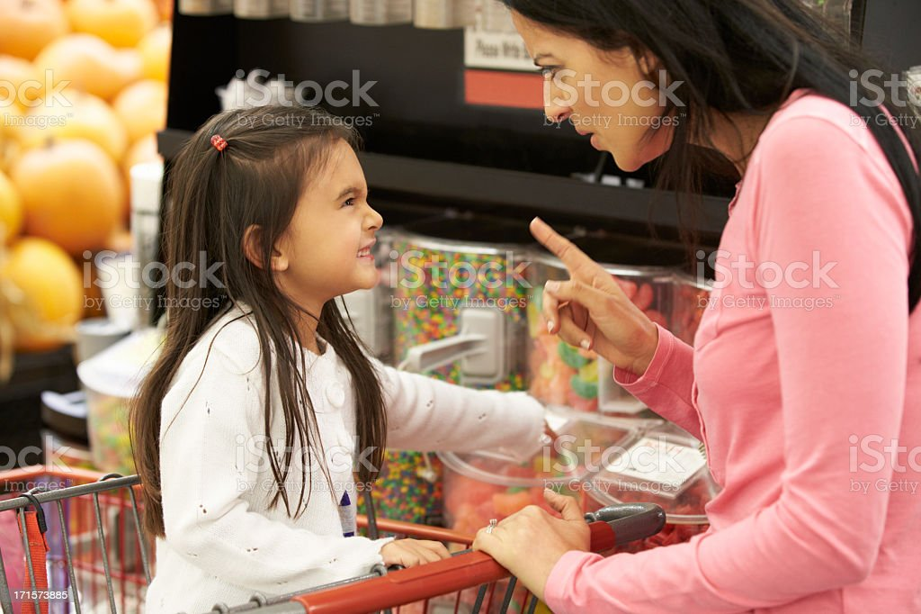 Girl Having Argument With Mother At Candy Counter stock photo