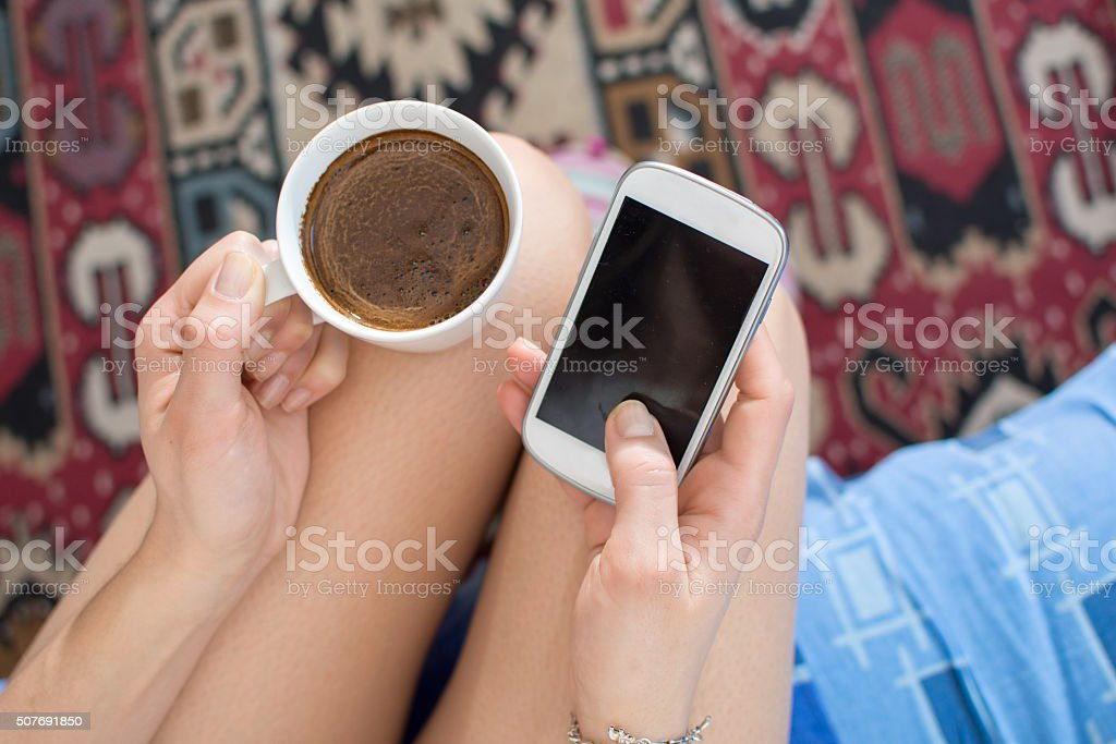 Girl  having coffee in bed holding smart phone stock photo