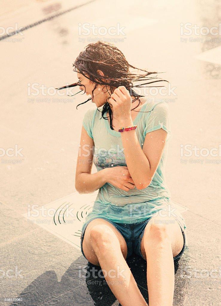 Girl having fun in a water fountain stock photo