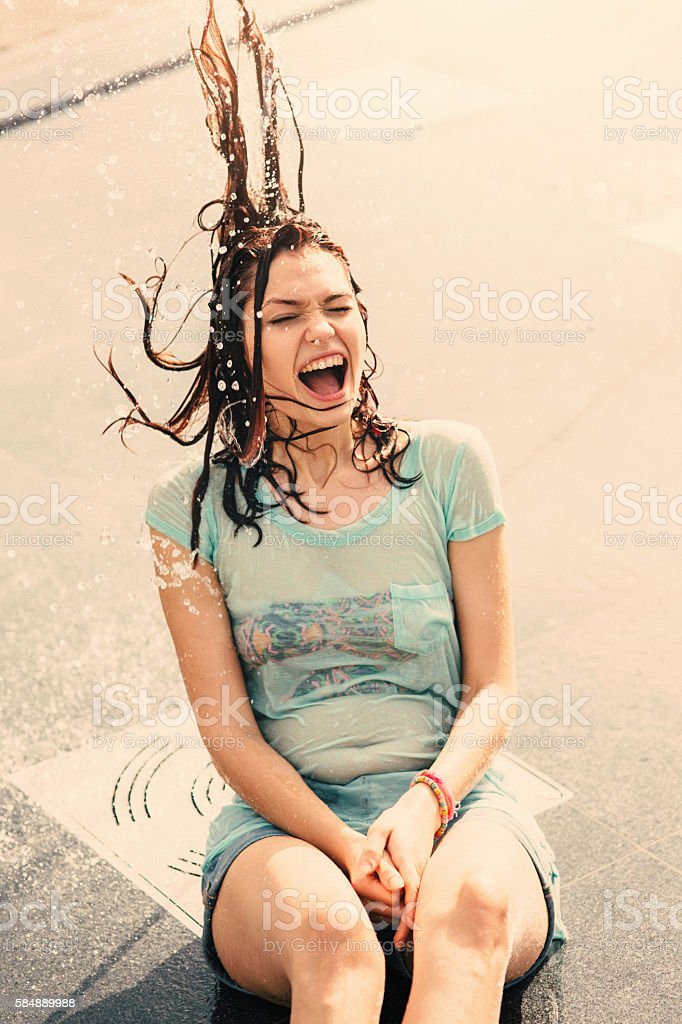 Girl having fun in a water fountain stock photo