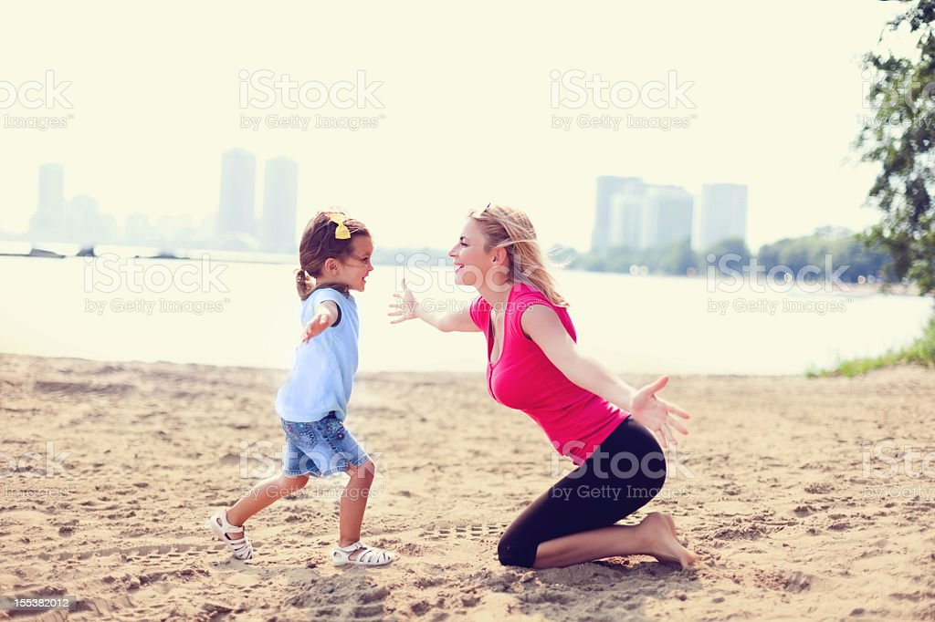 Girl having fun with her mother on a beach stock photo