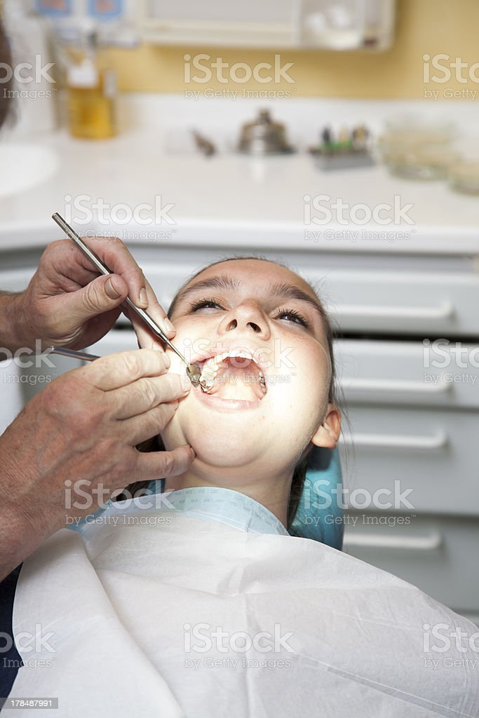 Girl having her teeth checked by doctor royalty-free stock photo