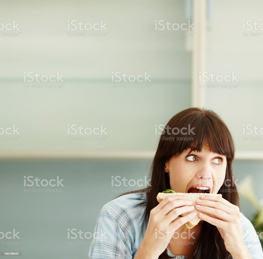 Girl having mouth open wide and munching a sandwich stock photo