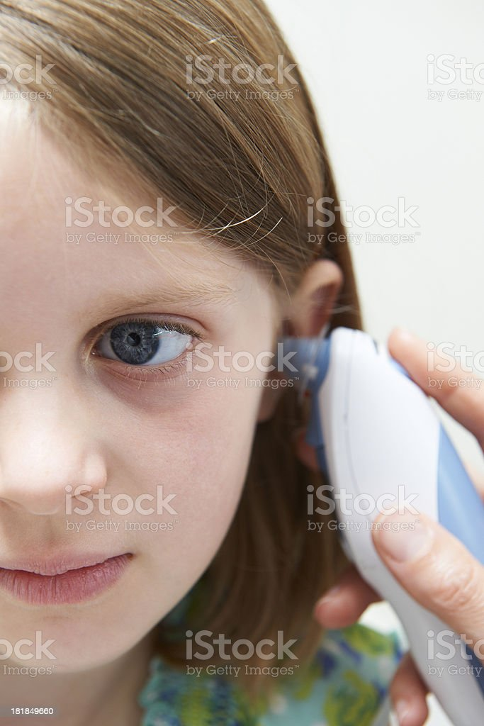 Girl Having Temperature Taken With Electronic Thermometer In Ear stock photo