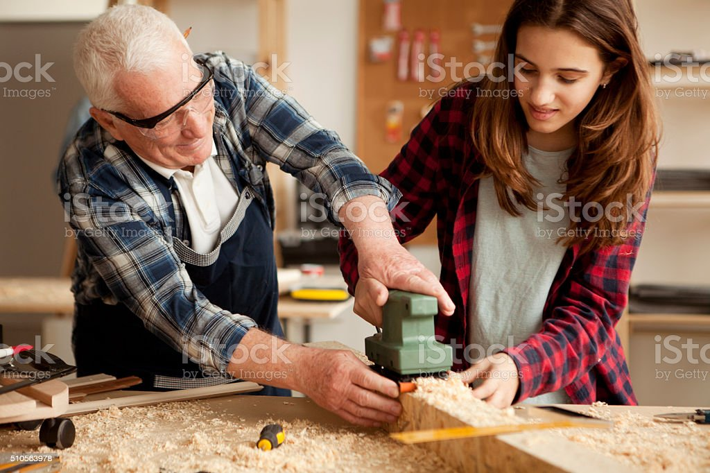Girl helping grandpa at woodshop stock photo