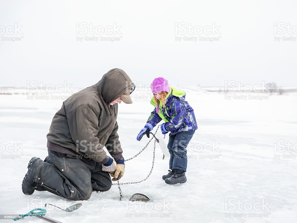 Girl Helping Grandpa Pull Up Minnow Trap in Winter stock photo