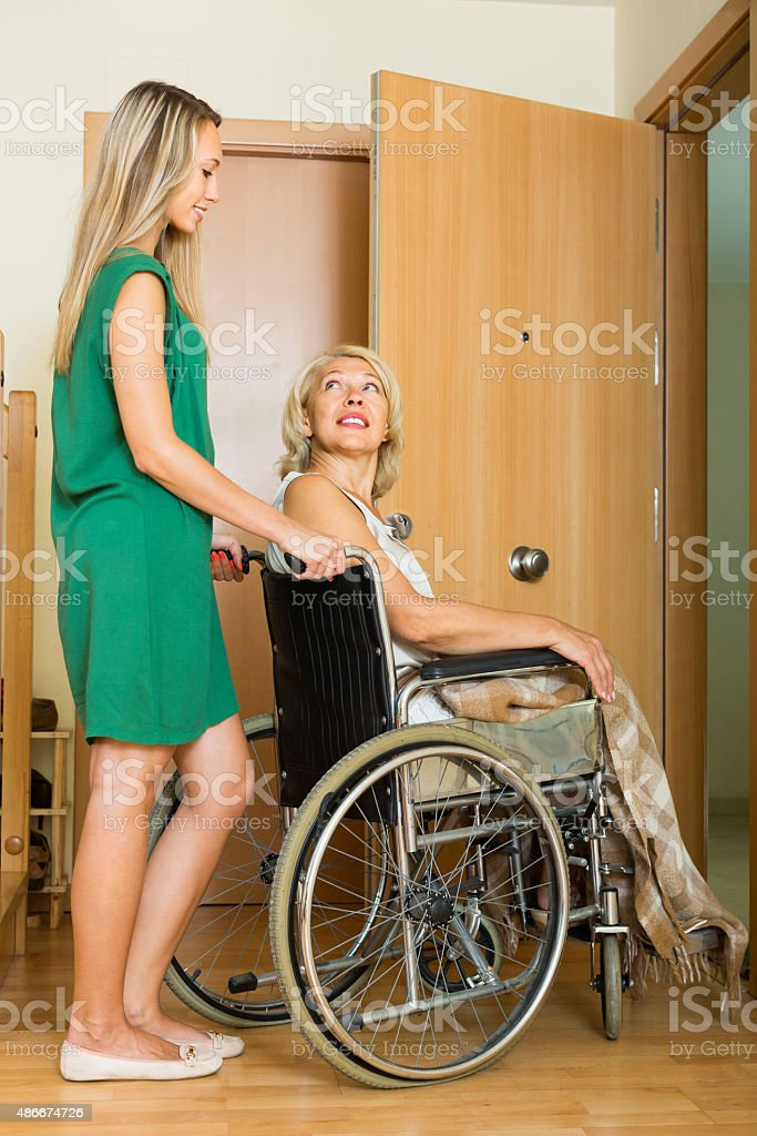 Girl helping handicapped woman stock photo