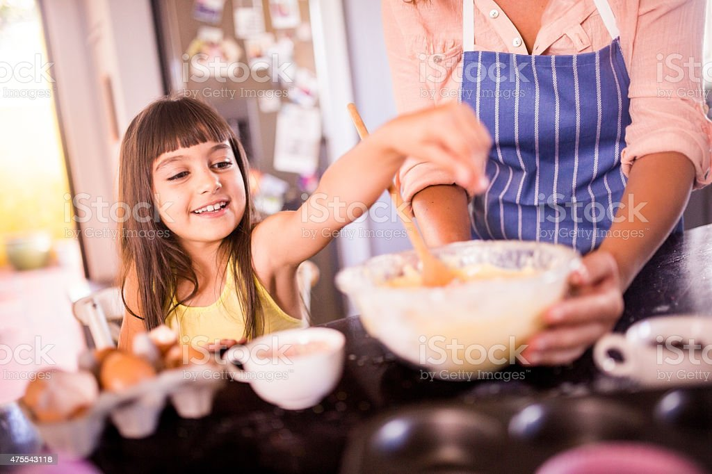 Girl helping mom in the kitchen to bake a cake stock photo