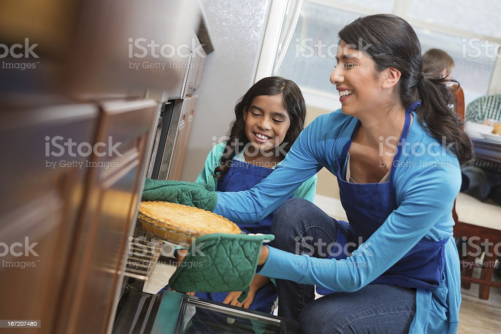 Girl helping mom take pie from oven in family kitchen stock photo
