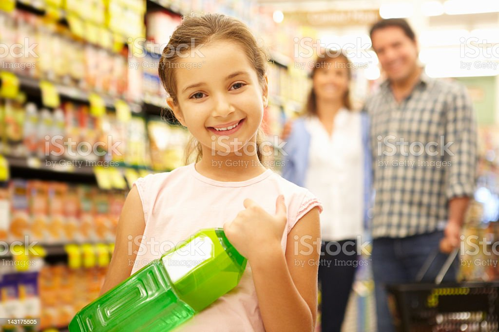 Girl helping parents with supermarket shopping royalty-free stock photo