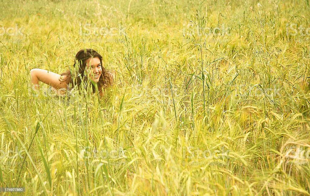 Girl hiding among wheat royalty-free stock photo