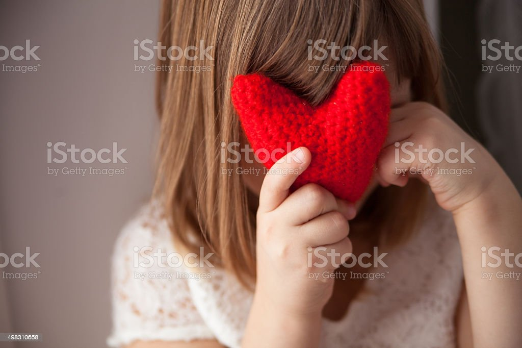 Girl hiding behind a knitted red heart, Valentine's Day, stock photo