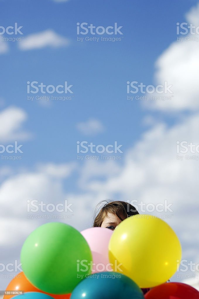 A Girl hiding behind the colorful balloons on a blue sky royalty-free stock photo